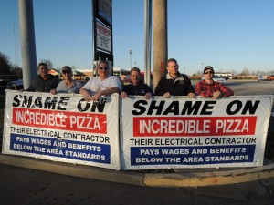 IBEW LOCAL 1 members who turned out to banner America's Incredible Pizza in South County included (from left) journeymen wiremen Chris Abele, Joe Wiese, Bryan Siebel, Kevin Fedke, IBEW Local 1 Business Representative David Roth and journeyman wireman Clifford Friend. – Labor Tribune photo