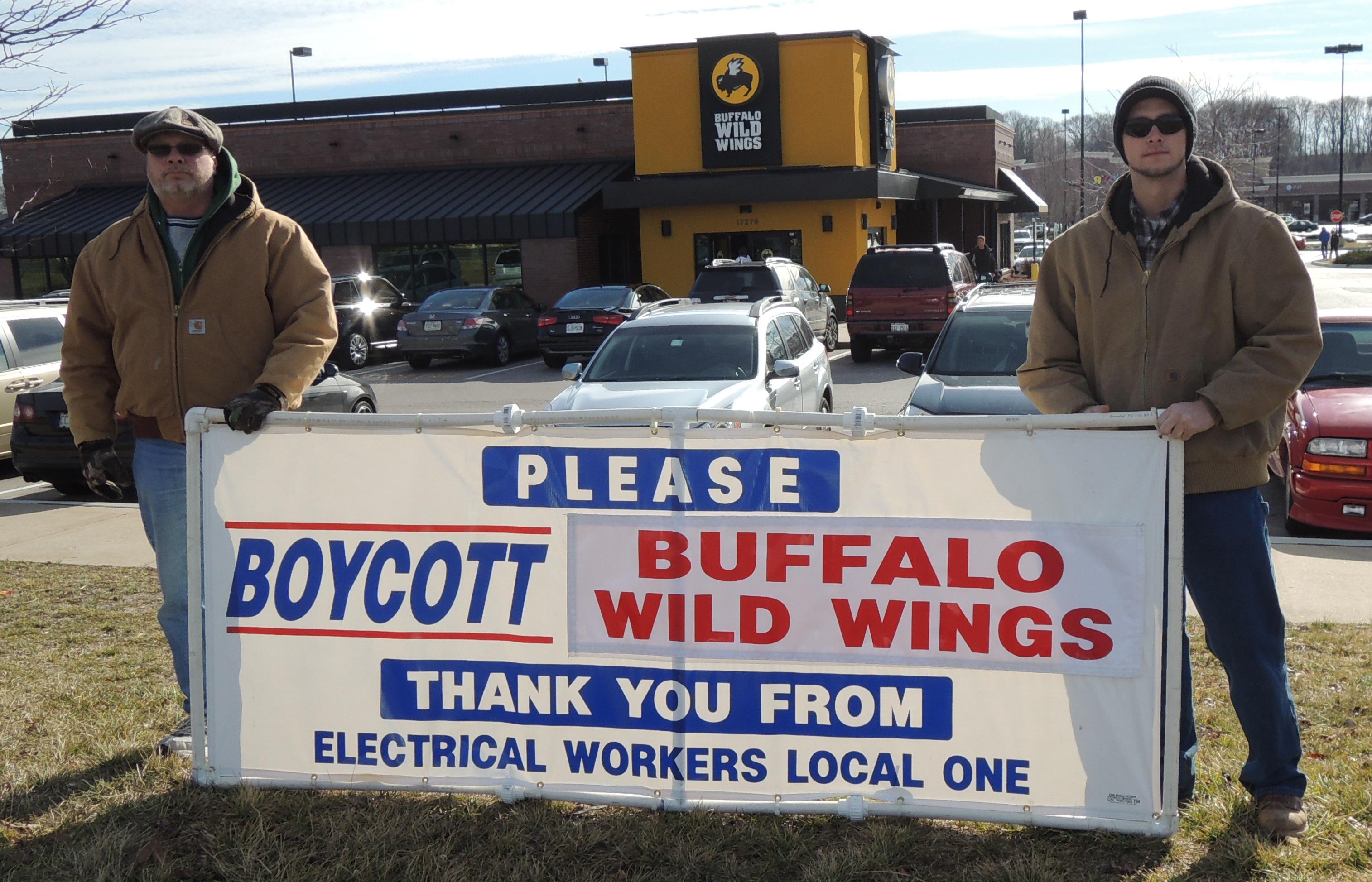 Journeyman Wireman Gregory Van Pelt Sr. (left) and his son Apprentice Gregory Van Pelt Jr. (right), bannered in front of the restaurant.