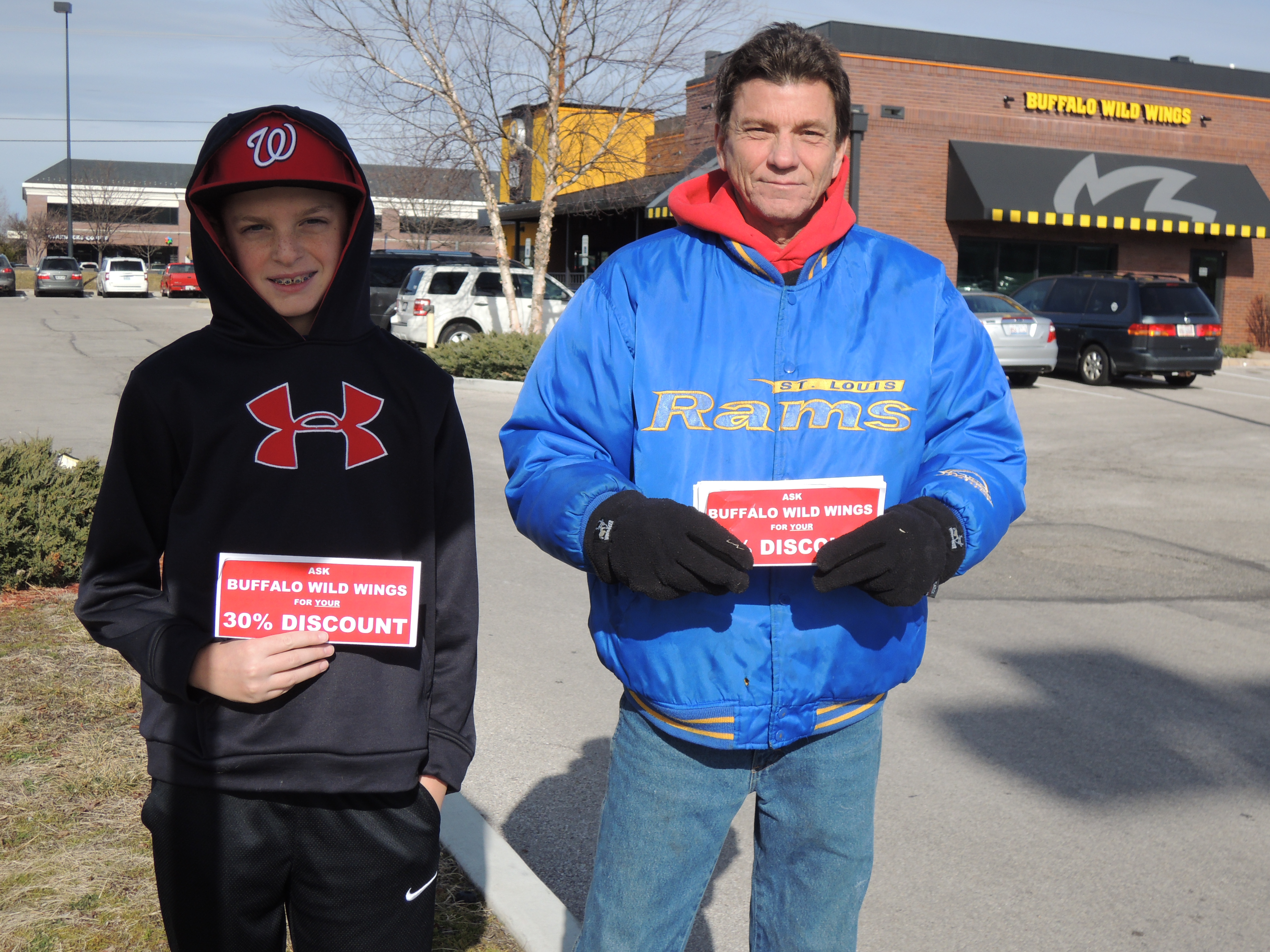 Raising public awareness to the issue, (LEFT PHOTO) Kyle Landwehr (left), the son of IBEW Local 1 Business Representative Ken Landwehr, and Lighting Maintenance Technician Darren Daniele handbilled customers pulling onto the parking lot of the chain's Chesterfield location