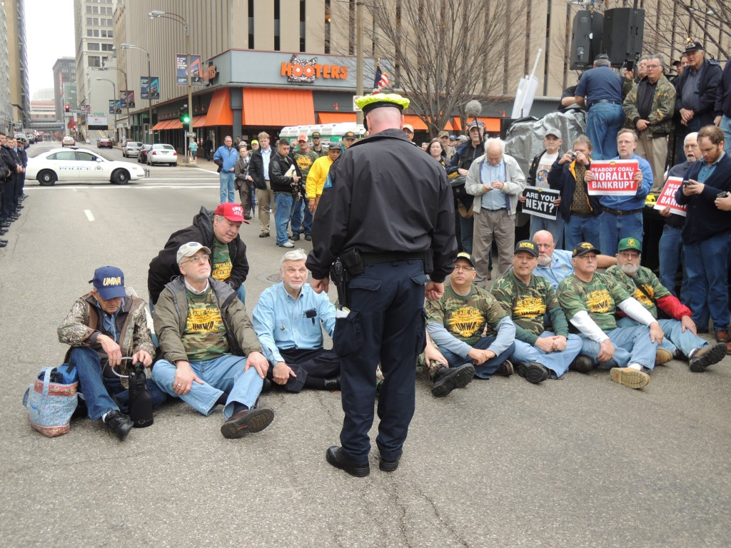 MOMENTS BEFORE THEY WERE ARRESTED, protesters with the United Mine Workers of America, including International President Cecil E. Roberts Jr. (seated third from left) blocked the street in front of Peabody Energy Corp. headquarters in St. Louis. Ten people, including Roberts, were arrested on a charge of failing to disperse. – Labor Tribune photo