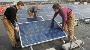 GOING GREEN at the St. Louis Electrical Industry Training Center, IBEW Local 1 electricians (from left) apprentice Joe Ruma, foreman and journeyman wireman Ron Plummer, and apprentice Bob Kertz, of Kaemmerlen Electric, recently installed a 100-panel solar array on the roof of the training center. The new array will help reduce the training center's energy costs, while providing training opportunities for journeymen and apprentices.  – Labor Tribune photo