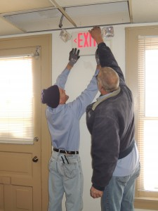 IBEW LOCAL 1 electricians (from left) Tom Lindsley and Kenny Wright, of Schaeffer Electric Company, install one of 10 combination exit signs/emergency lighting units at the new POW-MIA Museum at Jefferson Barracks.  – Labor Tribune photo