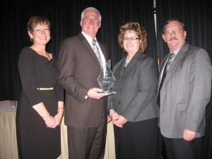 "LABOR HONORED: Dale Stewart (second from left), executive secretary/treasurer of the Southwestern Illinois Building & Construction Trades Council, accepted an award recognizing labor's partnership in delivering three large energy projects at the Leadership Council Southwestern Illinois's annual Salute to Southwestern Illinois Awards Dinner April 4. Presenting and accepting the award are (from left) Executive Director of the Leadership Council Ellen Krohne, (Stewart), Leadership Council President Ronda Sauget and President of the Building & Construction Trades Council Charles ""Totsie"" Bailey, business manager for Steamfitters Local 439.  –Labor-Tribune photo"