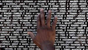 The hand of a visitor to the Vietnam Traveling Memorial Wall reaches out to touch the name of a family member who had died in the Vietnam War. AP Photo/Phil Coale