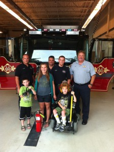 A BOY'S DREAM COMES TRUE. Nine-year old Parker Strobeck (in wheelchair) and his sister Abby and brother Mason were adopted for a day by Fire Fighters Local 2665 members in the Mehlville Fire Department, among them (from left) Captain Dave Waser, and privates Brian Torno, Tom Frasca and Joe Minnella. Parker is a former poster child/goodwill ambassador for the Muscular Dystrophy Association in the IAFF's four-state 2nd District. He had never been in a firehouse before.