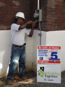 IBEW LOCAL 1 Journeyman Electrician Tim Blackwell puts the finishing touches on the electrical meter at Willie B. Lark's home in Pine Lawn. –Labor Tribune photo