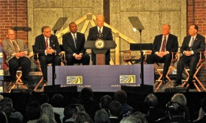 CALLING UNION WORKERS the backbone of American industry, Vice President Joe Biden (center, at the podium) visited America's Central Port in Granite City last week to mark the near completion of its South Harbor project, which was funded in part with $14.5 million in seed money from the federal American Recovery and Reinvestment Act of 2009. Joining Biden in celebrating the project and the federal investment in infrastructure were (from left) Madison Mayor and member of the Port Board of Commissioners John Hamm III, former U.S. Secretary of Transportation Ray LaHood, current U.S. Secretary of Transportation Anthony Foxx, (and to Biden's left) Illinois Gov. Pat Quinn and U.S. Rep. Bill Enyart (D-Belleville). – Labor Tribune photo