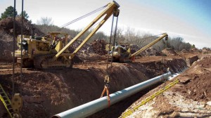 A 60-FOOT SECTION of pipe is lowered into a trench during construction of the Gulf Coast Pipeline in Prague, Okla., last year. The 485-mile Gulf Coast Pipeline is part of the Keystone XL project. Getty Images photo