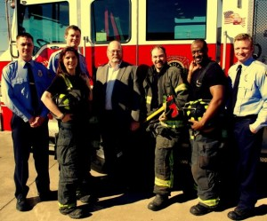 """MAKING A POINT that fire fighters and police officers were endorsing University City Council candidate Dennis Fuller (center), members of Fire Fighters Local 2665 dressed in their protective fire fighting equipment for a photo. City regulations define this dress as """"equipment;"""" however, University City is trying to determine if the fire fighters were in """"uniforms,"""" which regulations say cannot be used to promote political issues or candidates. The blue-shirted men are stand-ins for police officers, who joined with fire fighters to endorse Fuller and another council candidate. The city has threatened to fire the fire fighters if it is determined that they were in """"uniform."""""""