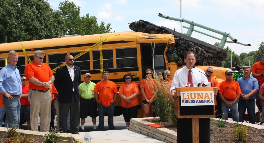 IT'S ABOUT JOBS AND SAFETY, St. Louis Mayor Francis Slay (at podium) explained to local media in a press conference sponsored by Laborers Local 110 to promote Amendment 7 on Missouri's Aug. 5 ballot, and urging Missouri's congressional delegation to move quickly to secure federal funding for the Highway Trust Fund. Behind the mayor, a staged school bus with its front crushed by a falling overpass. Standing at left (from left), State Rep. Dave Hinson, Eastern Missouri Laborers District Council Business Manager Gary Elliott and Missouri Laborers' Legislative Committee Legislative Director Adam McBride.   – Labor Tribune photo