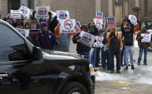 TALKING BACK: Union workers shouted and waved signs as Illinois Gov. Bruce Rauner left after speaking at the Decatur Club in Decatur, IL, last month.  Illinois labor unions filed a lawsuit last week seeking to invalidate an executive order Rauner issued Feb. 9 ending a requirement that state workers pay a fair share fee for contract negotiations if they choose not to join the union in their workplace. – Hugh Sullivan/AP photo