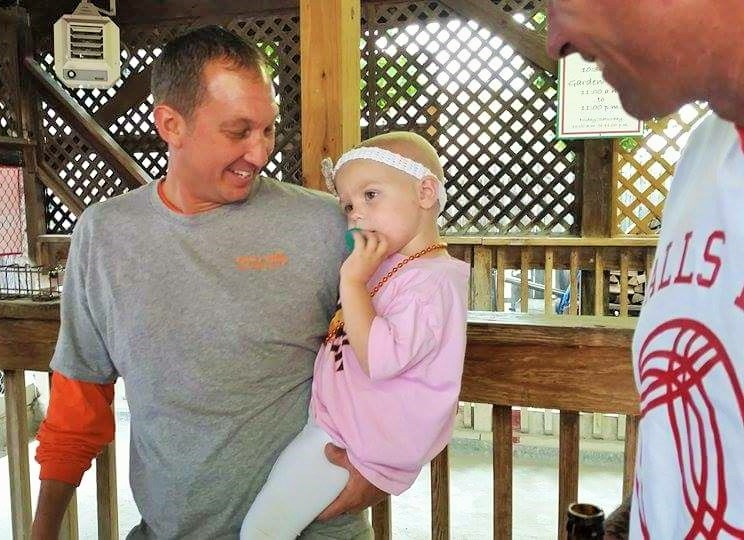 PROUD PAPA: Bryan Keith holds his 2-year-old daughter Vivian after opening presents from Ironworker Brad Singleton at a Sept. 26. event at Milo's Bocce Garden to help offset costs for the toddler's ongoing medical expenses. – Greg Combs, Ironworkers 396 photo