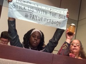 PROTESTERS Nabeehah Azeez (left) and Basmin Nadra hold up a banner and a sample of contaminated mine water during the bankruptcy hearing. – Caitlin Lee photo.