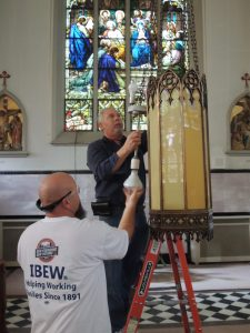 """THERE TO HELP: Brian Caldwell (in the white IBEW t-shirt) and Mitch Klein (on the ladder), both of IBEW Local 11 in Los Angeles, replace the lighting in one of the ornate fixtures at Our Lady of the Holy Cross. """"We do this year round,"""" Klein said. """"If someone is in trouble or someone is in need and they can't afford an electrician, we're there to help."""" – Labor Tribune photo"""