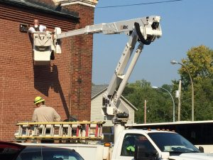 IBEW VOLUNTEERS, in town for the IBEW convention, install new security lighting outside the gymnasium at Our Lady of the Holy Cross in Baden, MO, as part of the IBEW's Day of Service. - Labor Tribune photo