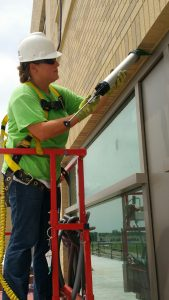 LEARNING THE TRADE: Julie Koch, a Bricklayers and Allied Craftworkers Local 1 apprentice, caulks a window while on the job at St. Elizabeth's Hospital in O'Fallon, IL. Koch hopes to someday be president of Allied Waterproofing, a family-owned business founded by her grandfather. – Bricklayers Local 1 photo