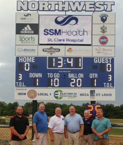 SCORING FOR STUDENTS at the Aug. 26 dedication of the new Northwest R1 High School digital scoreboard were (from left) David Brand Jr. of Piros Signs, IBEW Local 1 Business Representative Chuck DeMoulin, Northwest R1 School District Superintendent Paul Ziegler, IBEW Local 1 Business Manager Frank Jacobs, IBEW/NECA Director of Governmental Affairs Tim Green, IBEW/NECA and Billy Winkler, owner of Five Star Electric. – Compass Communications photo